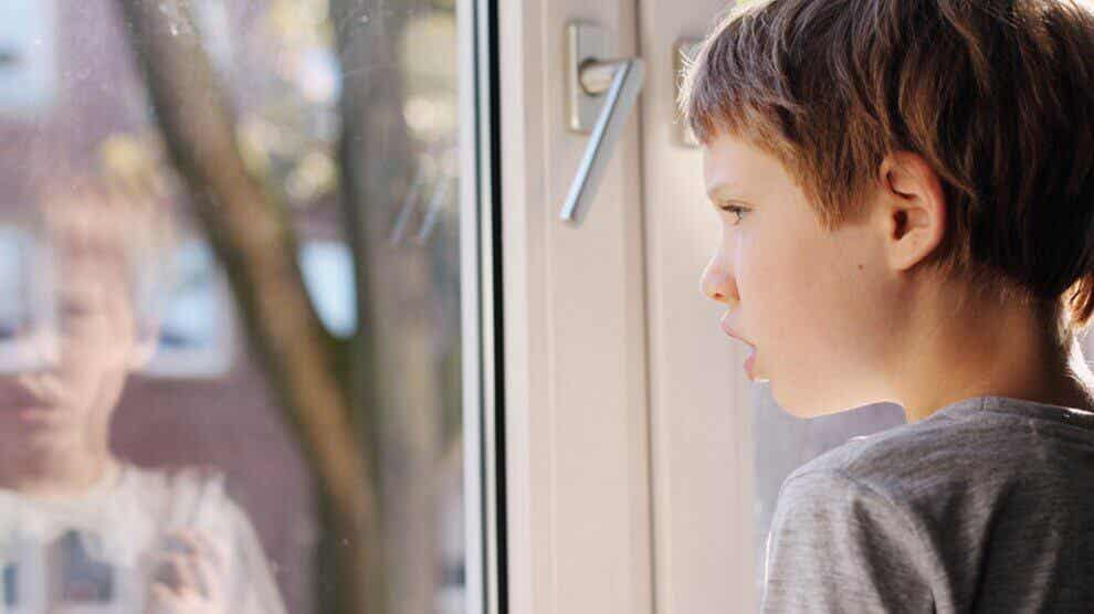 A child with autism looking out a window.