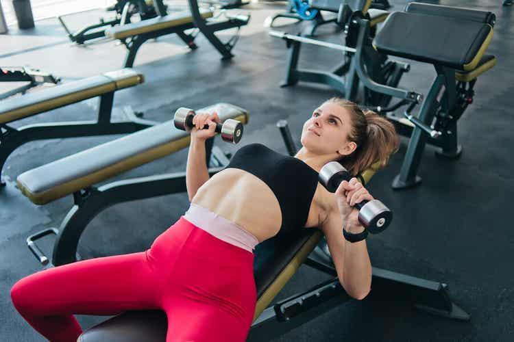 Spor salonunda ağırlık kaldıran bir kadın.