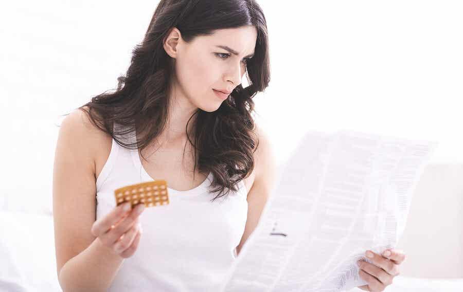 A woman reading information regarding her birth control pills.