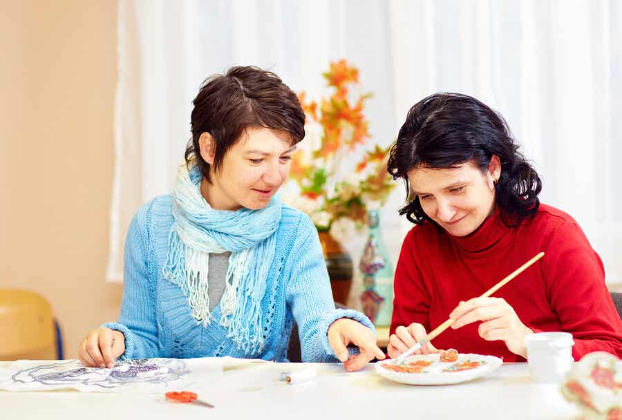 Two women doing crafts at a table.