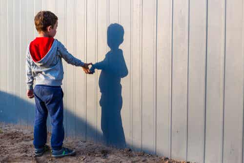 A child pointing to his shadow on a wall.