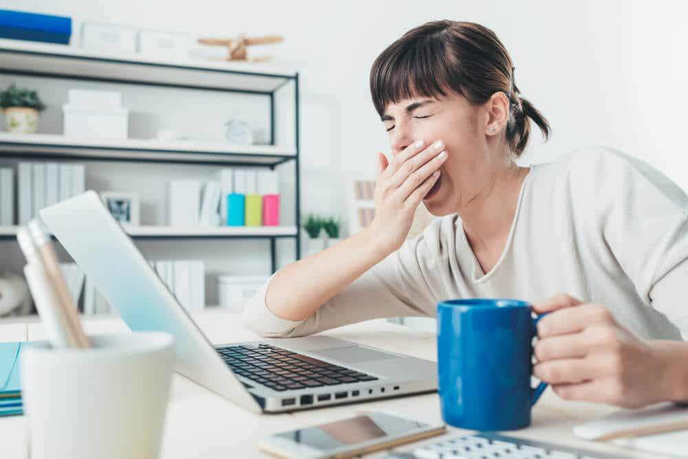 A woman yawning while working on her laptop.