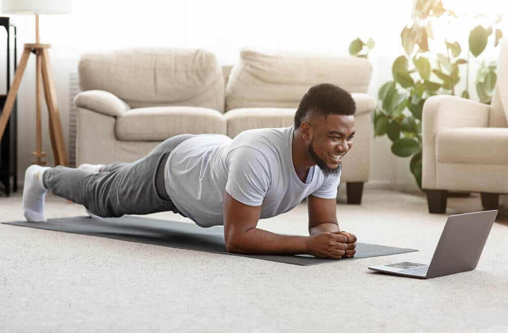 A man exercising at home with a laptop.