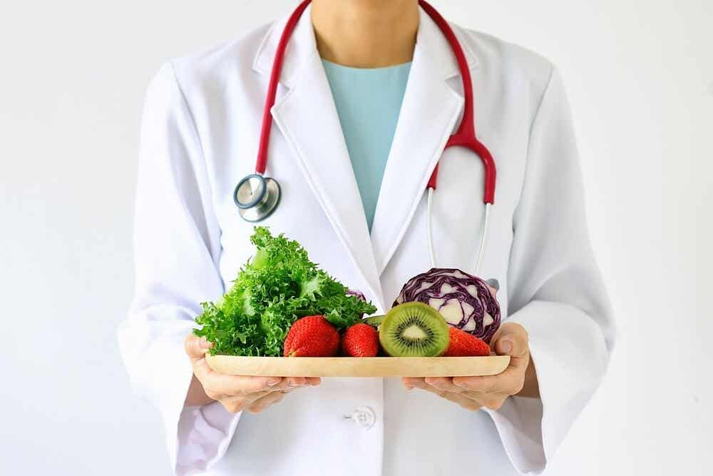 A doctor holding a cutting board full of fruits and vegetables.
