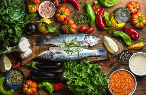 Fish on a cutting board, surrounded by vegetables, spices and legumes.