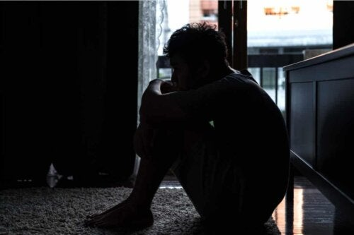 Person sat on the floor in the dark sad and depressed.