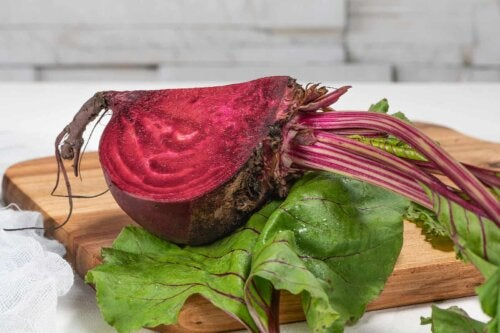 Quarter of a beet on a chopping board with a leaf.