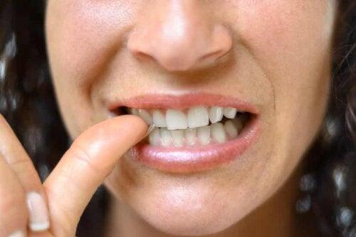 woman biting nail close up