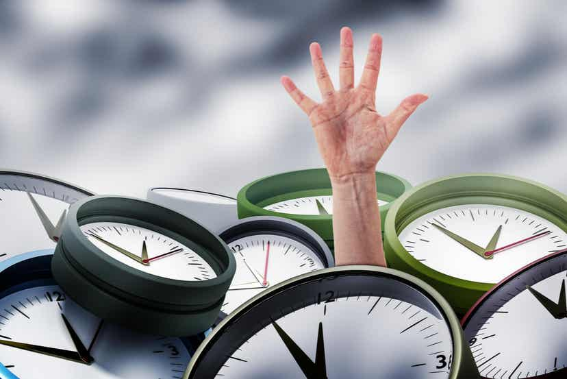 A hand reaching out from under a pile of clocks.