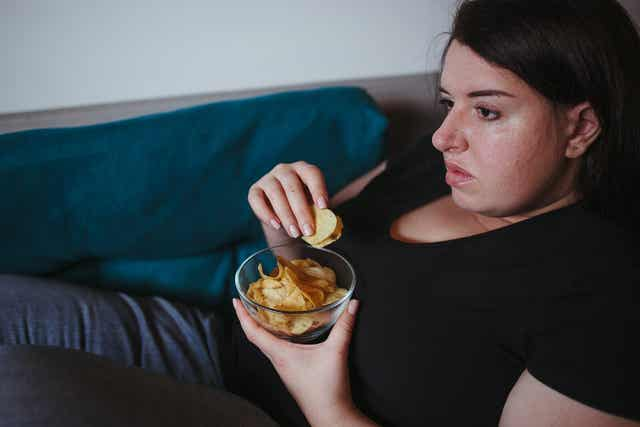 Sitzender Lebensstil - Eine Frau isst einen Snack auf der Couch.