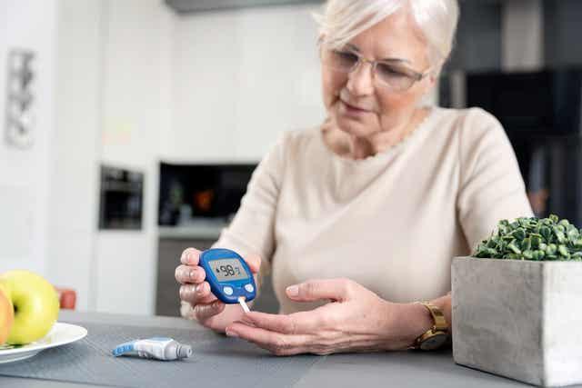 An elderly woman checking her blood sugar.