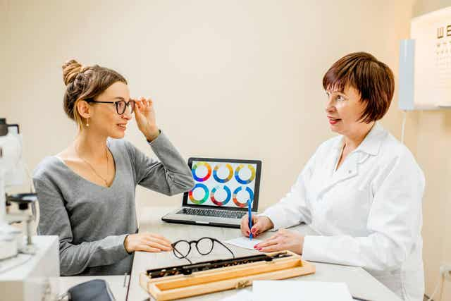 Bir hastayla konuşan bir göz doktoru.