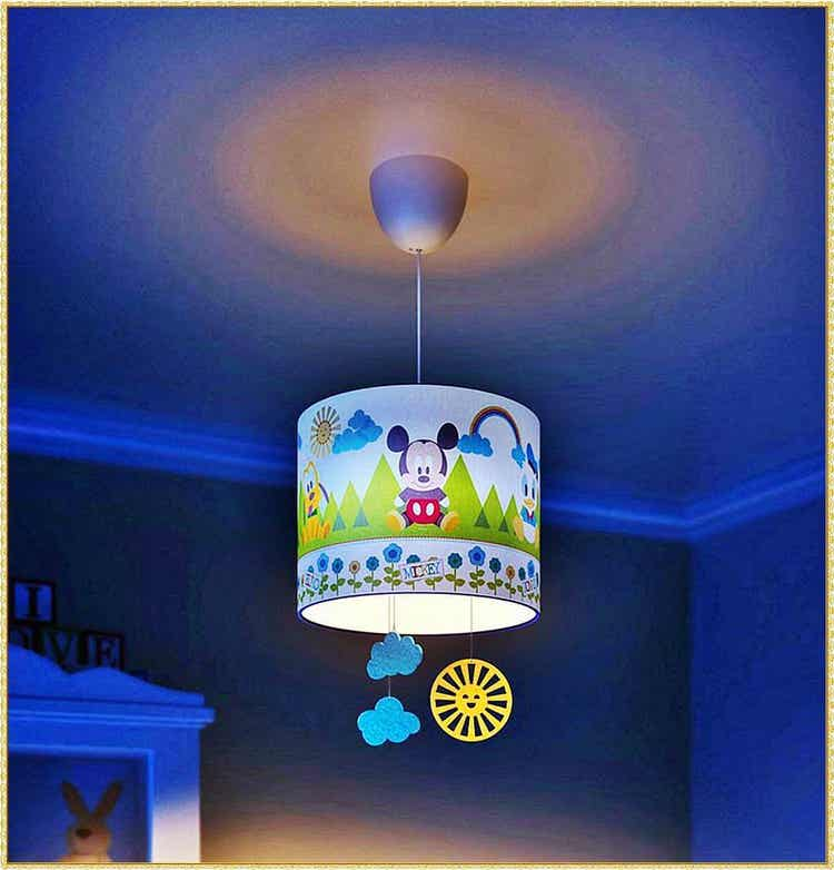 A mickey mouse lampshade in a baby's room.