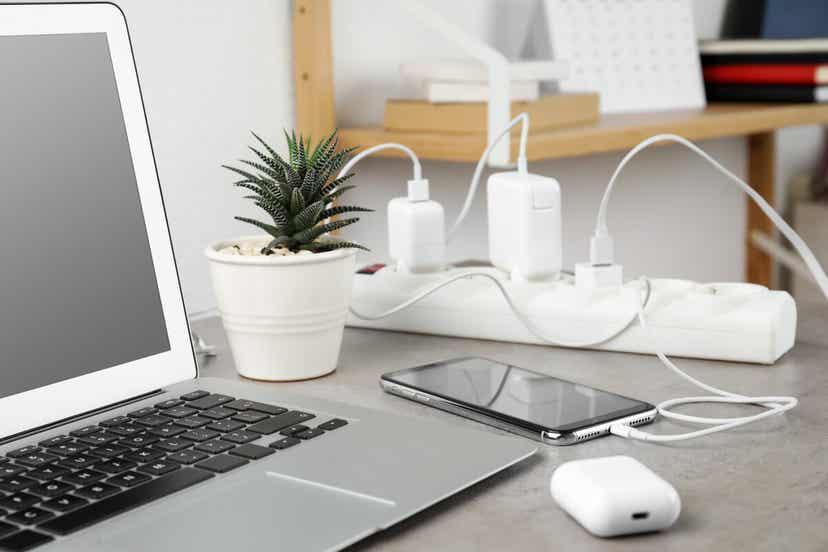 Bir masanın üzerindeki bir anahtarlı uzatma kablosuna takılı şarj cihazları.