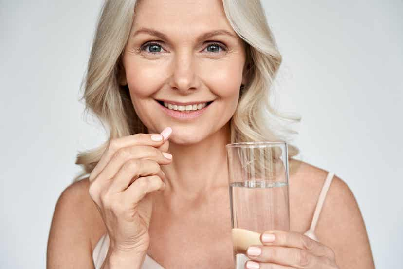 An older woman taking a pill with water.