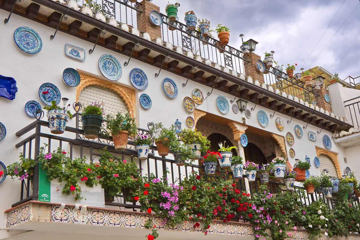 A balcony in Andalusian covered with ceramic flower pots and plates.