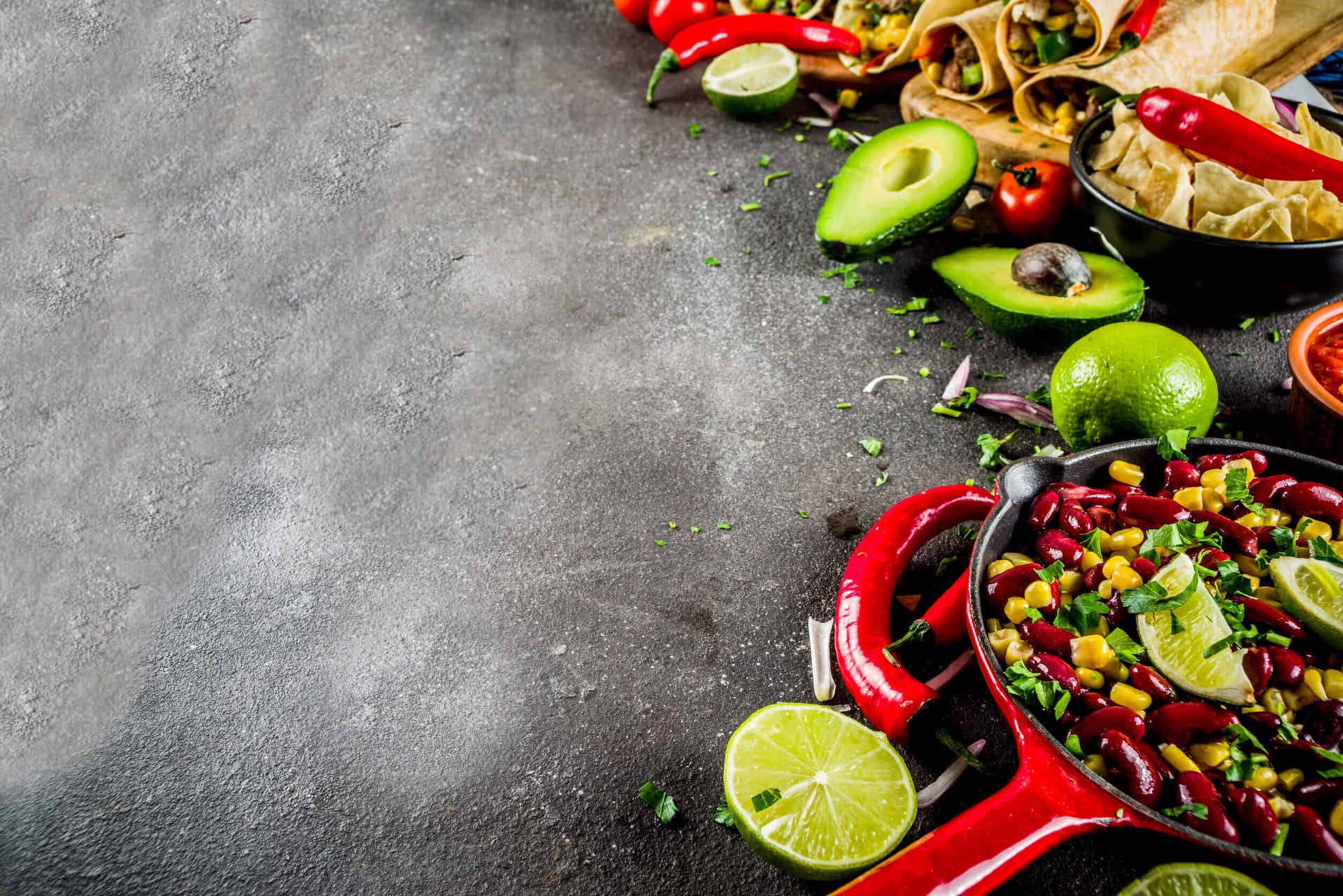 A skillet, bowl, and cutting board, all full of fresh Mexican foods made of beans, fruits, and vegetables.