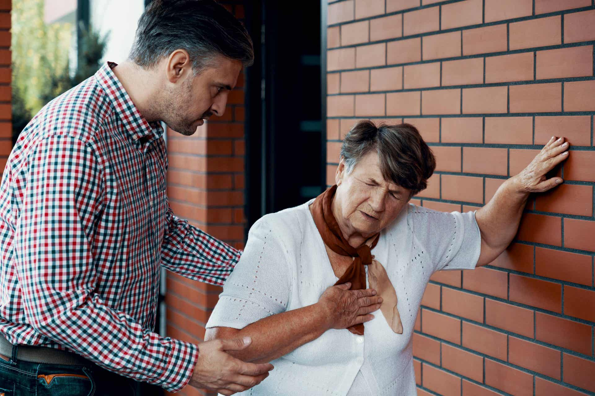 A man assisting an elderly woman who's not feeling well.