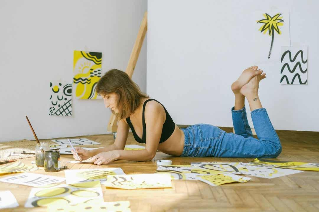 A woman lying on the floor painting, alone.