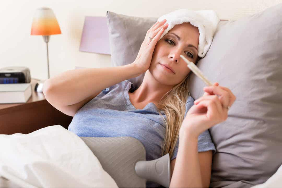 A woman lying in bed with a fever, taking her temperature.
