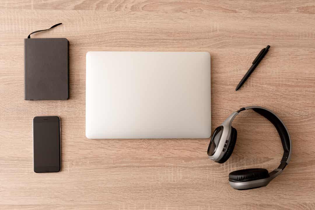 A planner, a smartphone, a laptop, a pen, and headphones neatly arranged on a desktop.