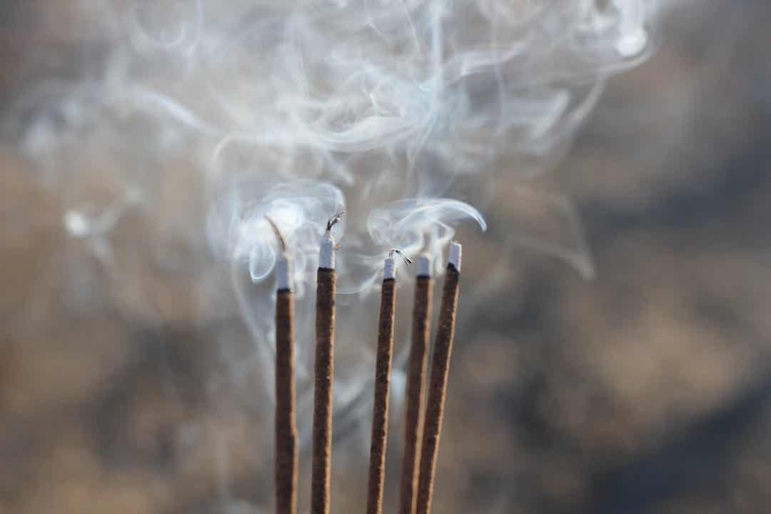 A row of burning incense sticks.