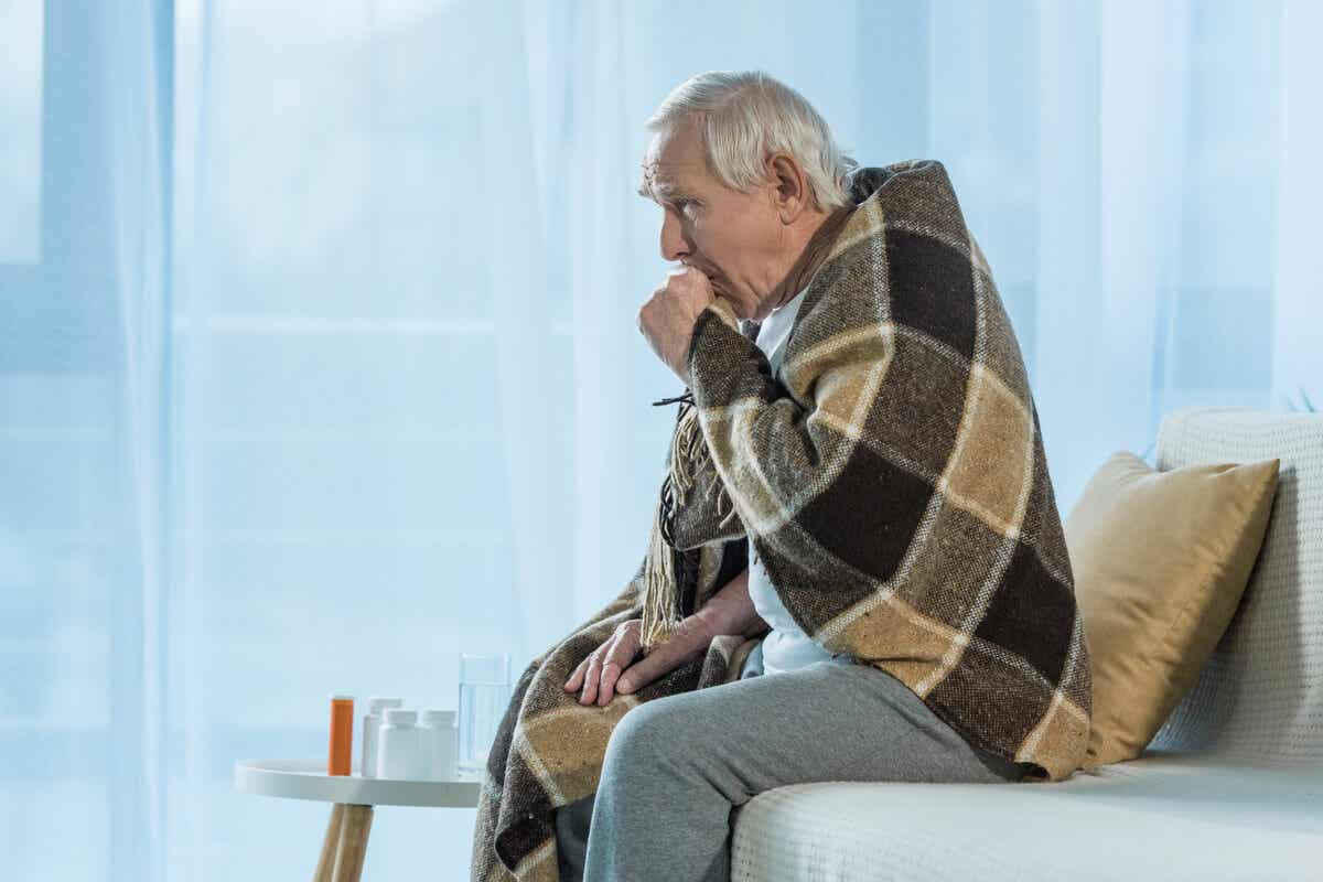 An elderly man with a blacked over his shoulders, coughing into his hand.