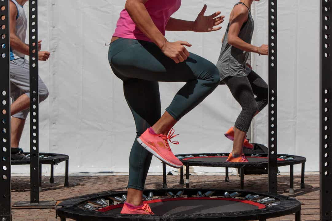 Mehrere Erwachsene trainieren auf einzelnen Trampolinen.