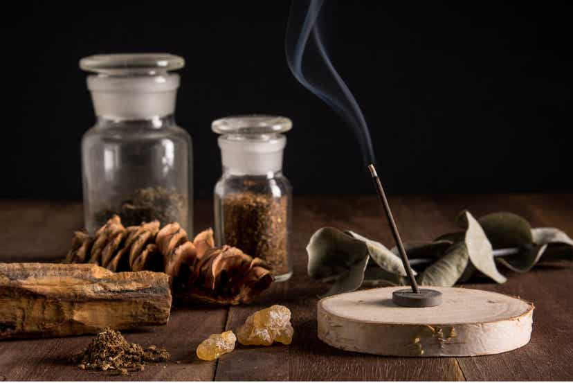 An incense burner surrounded by different objects from nature, including amber, a eucalyptus branch, and a pine cone.