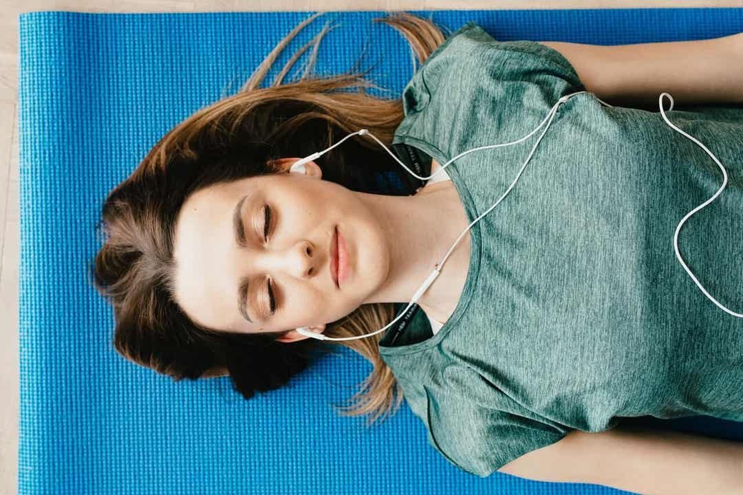 A woman lying on a mat with her eyes closed, listening to headphones.