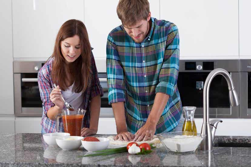 A couple making homemade pizza.