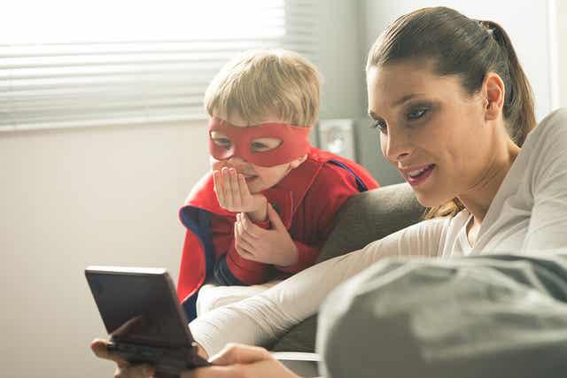 En kvinde, der sidder i sin stue og kigger på en digital enhed med et barn