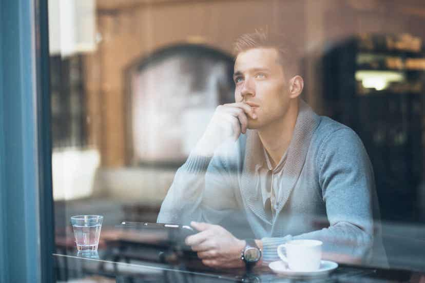 A man sitting in a cafe, thinking about his future.