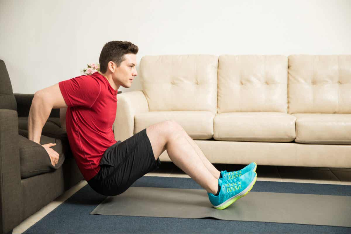 A young man performing tricep dip exercises with his hands on the seat of his couch and his feet on the floor ahead of him.