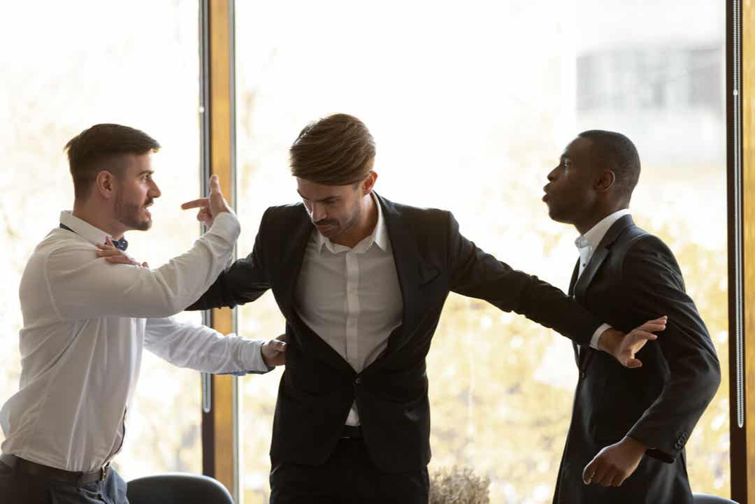 A man separating two fighting coworkers.