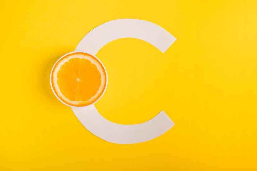 En halv appelsin foran et C