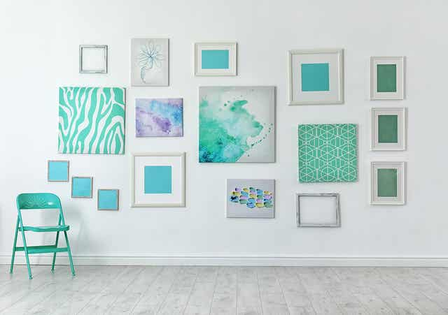 An arrangement of teal-colored artwork on a wall.