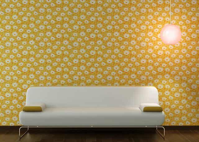 En hvid sofa foran en væg dækket af gul tapet med hvide blomster