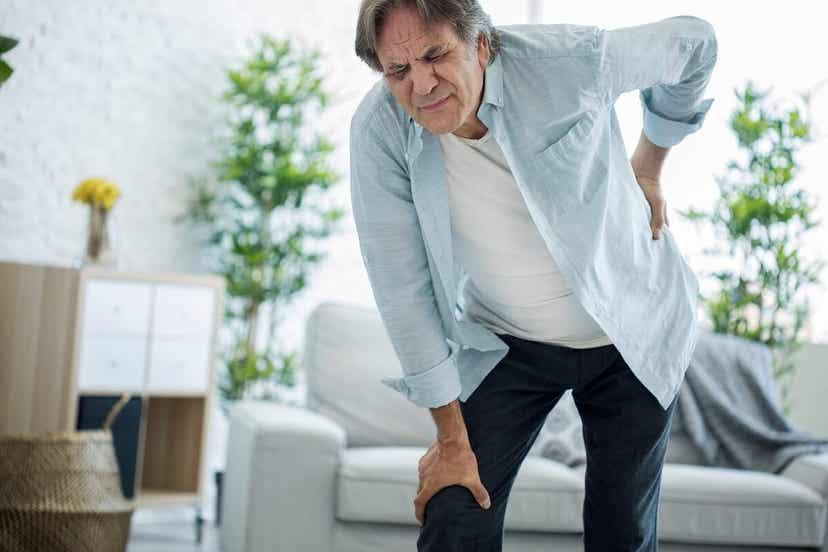 En mand med nyresmerter, der tager sig til ryggen