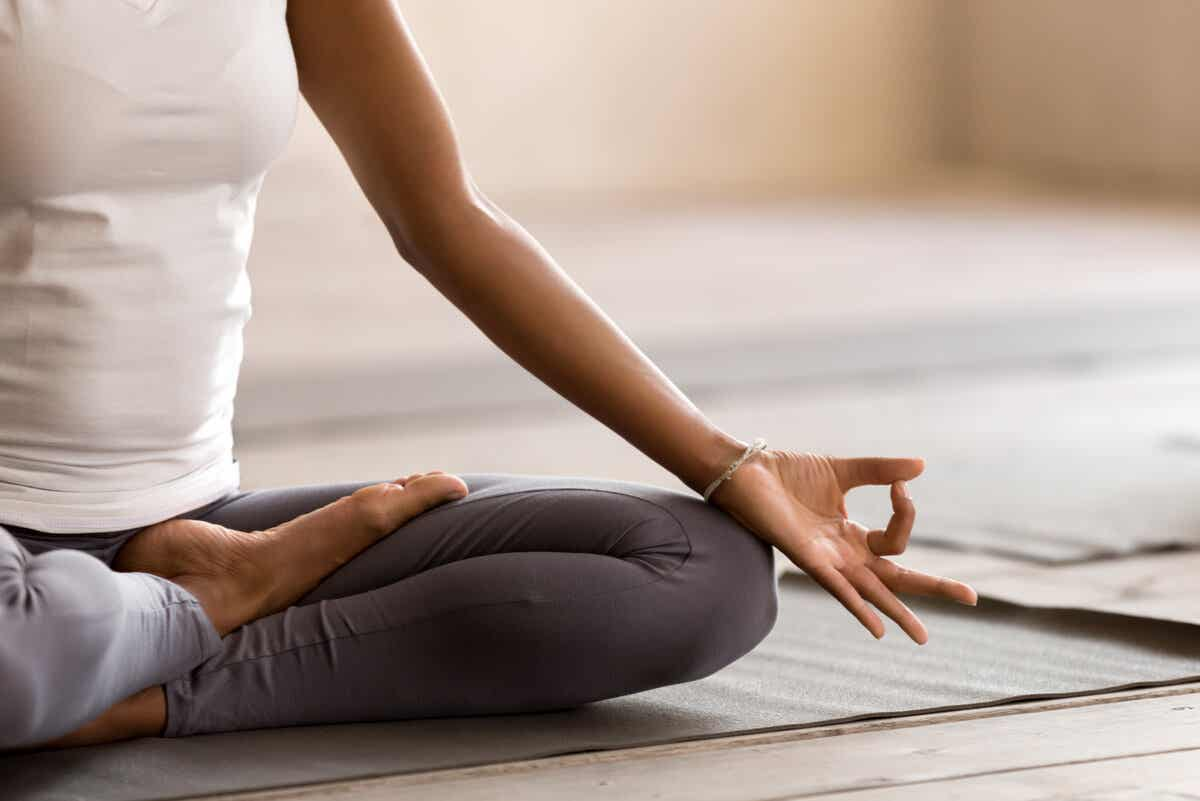 close up of a woman's hand and knee whilst she sits on the floor meditating