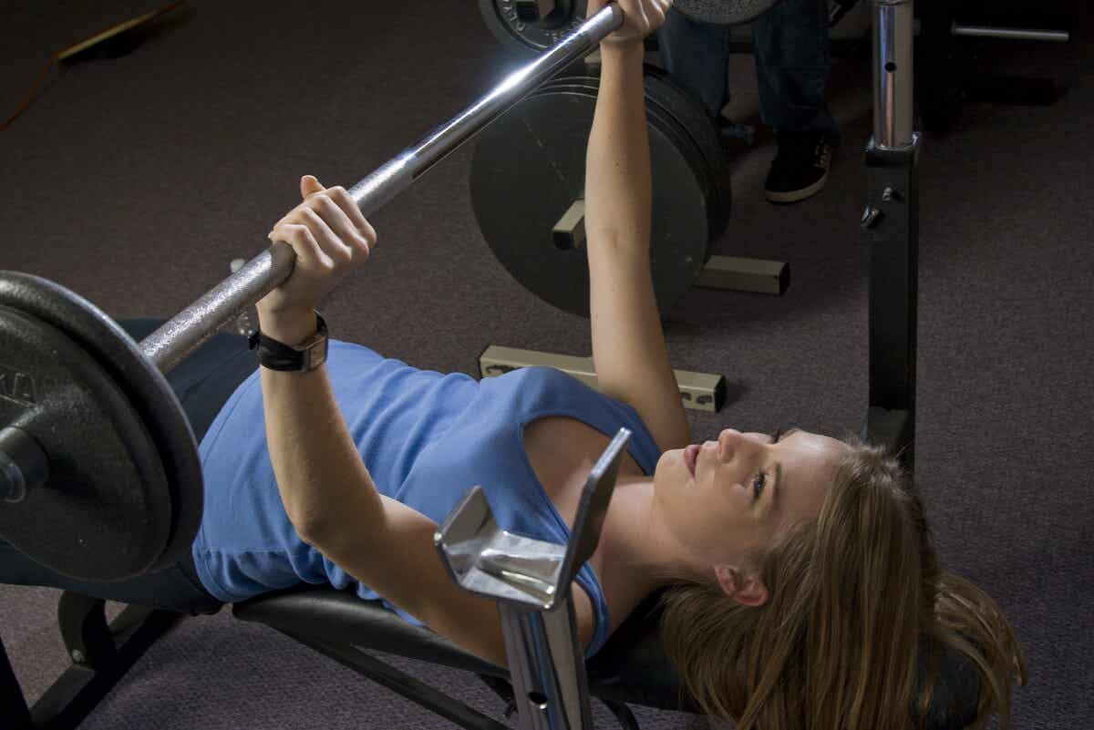 A woman performing a flat bench press.