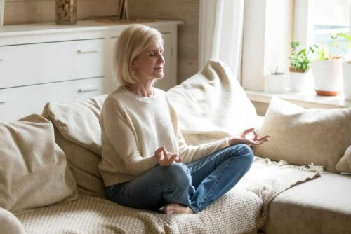 woman meditating in her home sat on the floor with her eyes closed