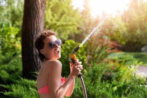 Smilende kvinde leger med vandslange