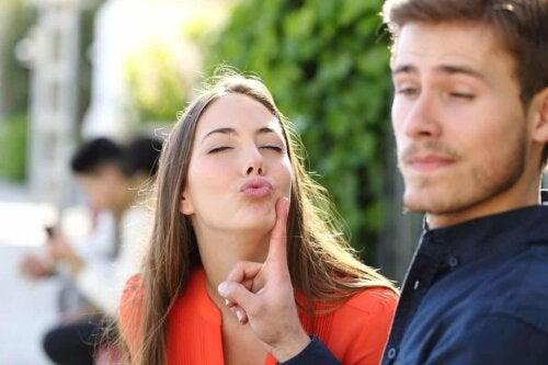 En kvinne som prøver å kysse en mann.
