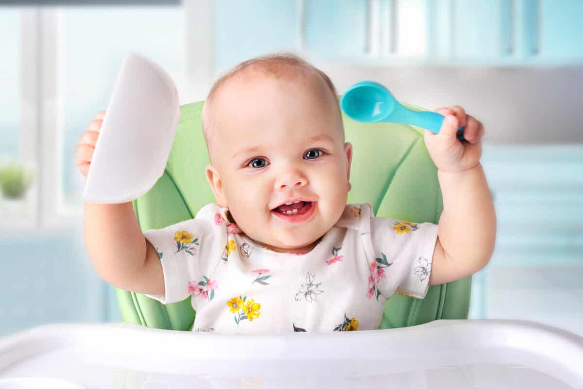 A baby holding her bowl and spoon in the air.