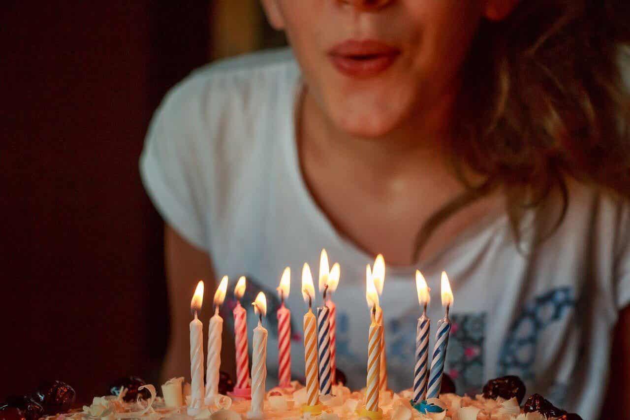 En kvinne som blåser ut lysene på en kake.