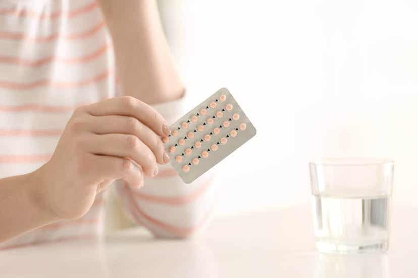 En kvinne som holder en blisterpakning med p -piller.