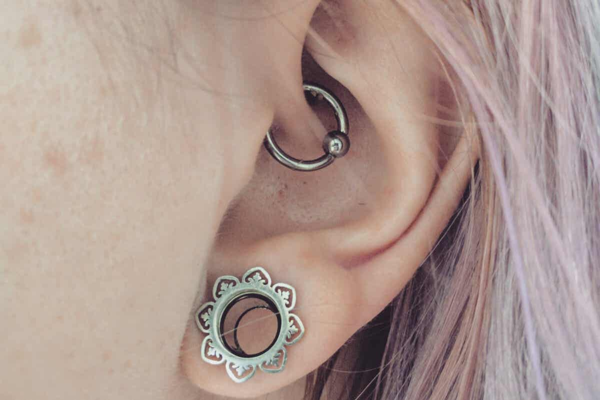 A woman with 2 different types of piercings in her ear.