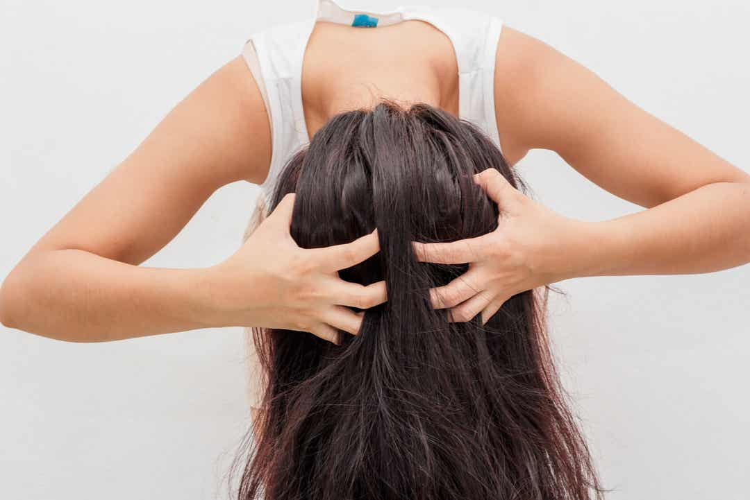 A woman with long hair scratching her scalp.
