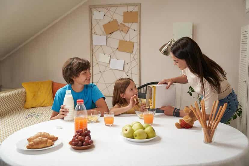 En mor som serverer frokost til sønnen og datteren.